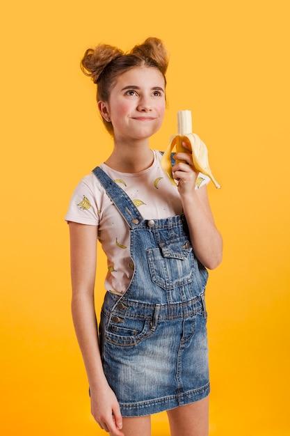 Вид сбоку девушка ест банан Бесплатные Фотографии