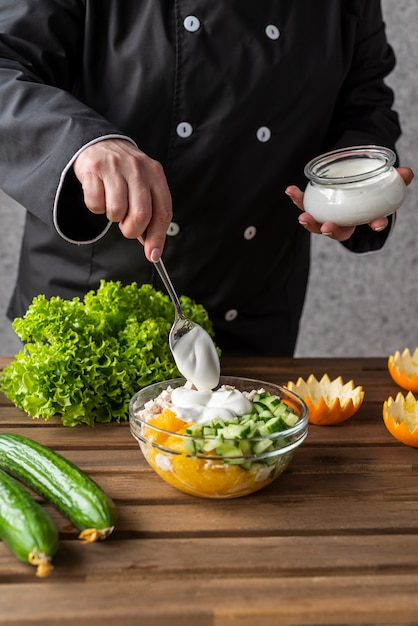 サラダにドレッシングを追加するシェフ 無料写真