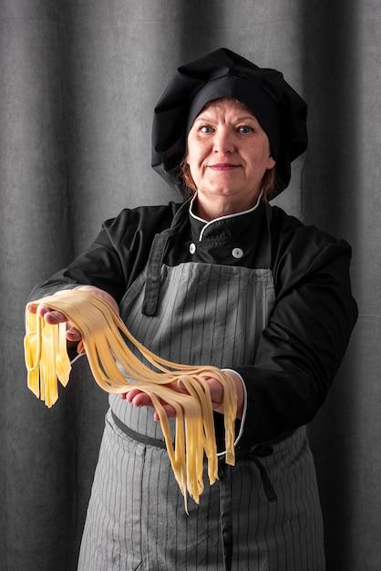 Смайлик шеф-повар держит свежую пасту Бесплатные Фотографии