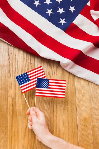 Вид сверху руки, держащей американские флаги Бесплатные Фотографии