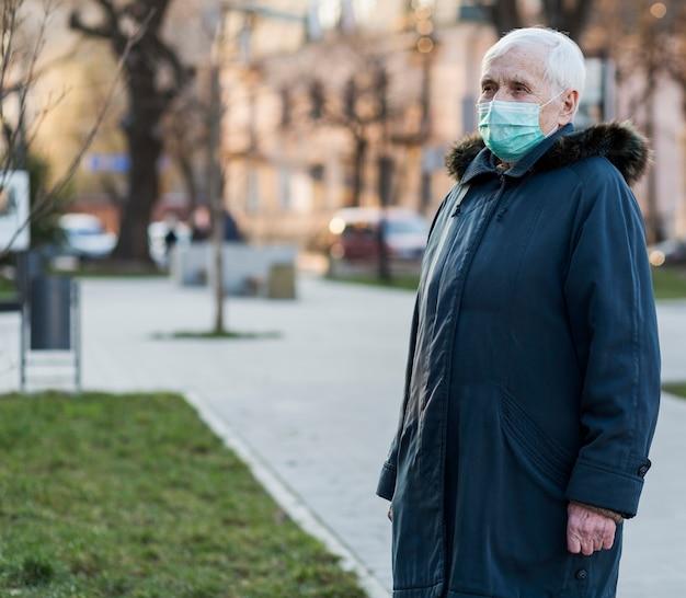 医療マスクを身に着けている老婆の側面図 無料写真