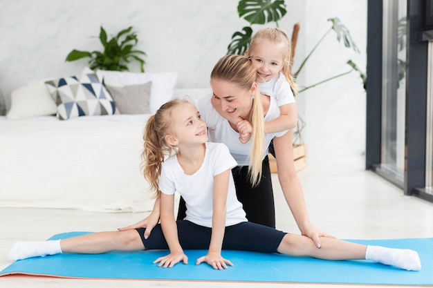 Счастливая мать и дочери дома на коврик для йоги Бесплатные Фотографии