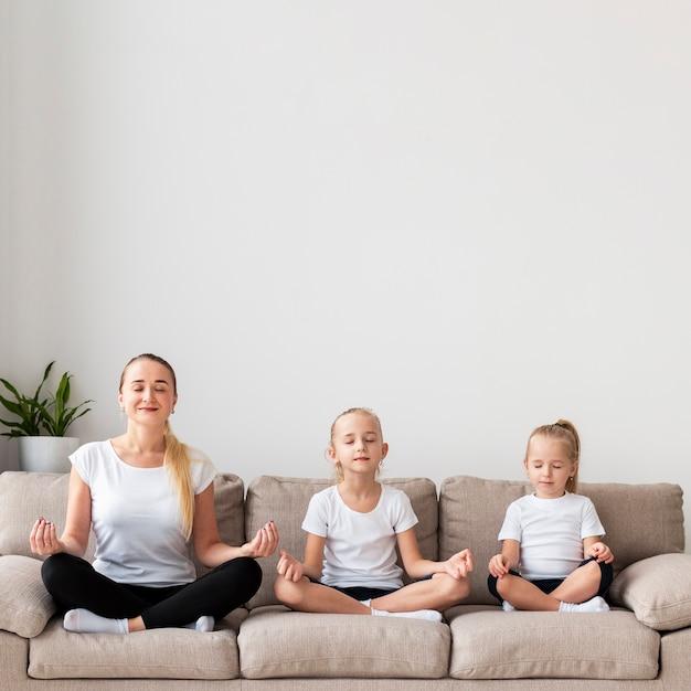 母と娘が自宅のソファで瞑想 無料写真