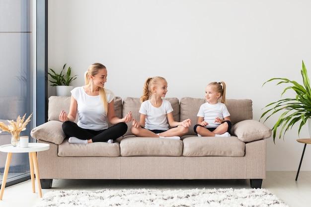 Матери и дочери тренируются дома на диване Бесплатные Фотографии