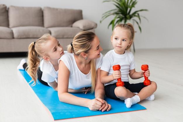 Мать позирует с дочерьми на коврик для йоги дома Бесплатные Фотографии