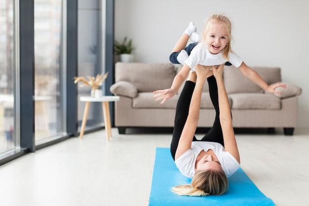 自宅でスマイリーの子供と運動する母親の正面図 無料写真