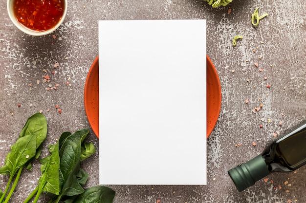 Вид сверху пустой меню бумаги на тарелку со шпинатом и оливковым маслом Бесплатные Фотографии