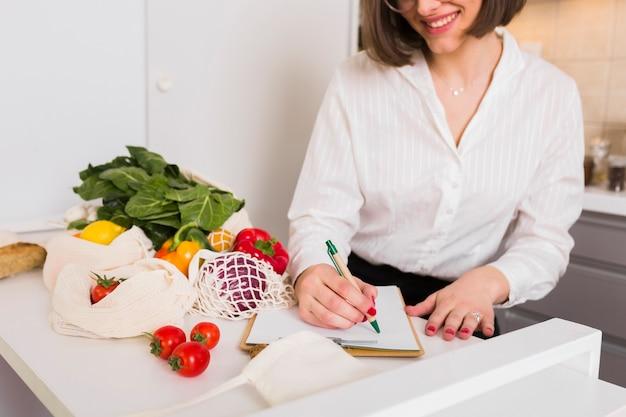 Молодая женщина проверяет список продуктов Бесплатные Фотографии