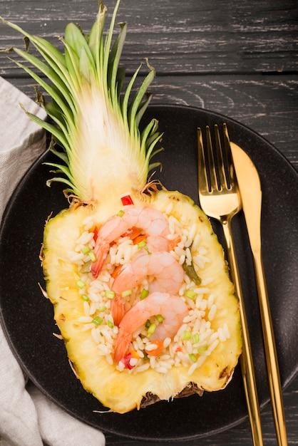 Вид сверху половина ананаса с креветками и золотыми столовыми приборами Бесплатные Фотографии