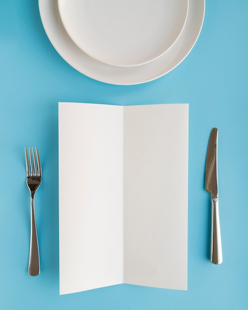 Вид сверху пустой меню бумаги с тарелками и столовыми приборами Бесплатные Фотографии