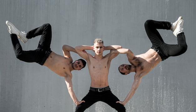 外で踊りながらポーズをとって上半身裸のヒップホップのパフォーマーの正面図 無料写真