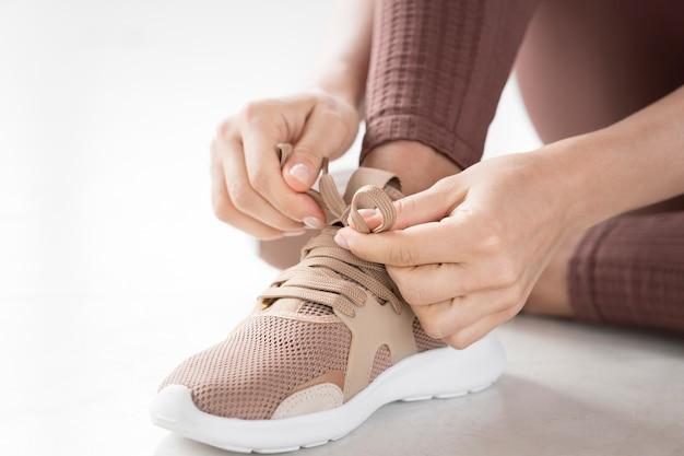 Крупным планом вид рук и спортивной обуви Бесплатные Фотографии