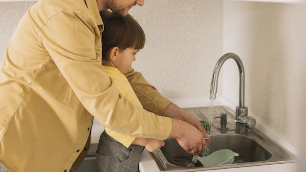 父と息子がカトラリーとお皿を掃除 無料写真