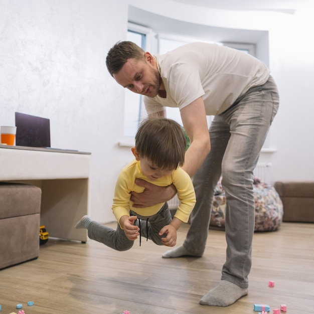 Отец играет и держит своего сына Бесплатные Фотографии
