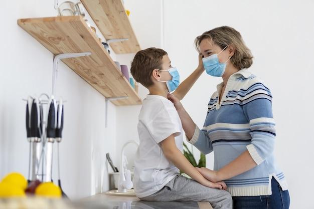 母と息子の医療マスクを着用の側面図 無料写真