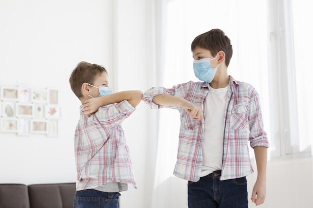 Дети трогают локти внутри и носят медицинские маски Бесплатные Фотографии