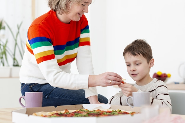 Мать дает ребенку дезинфицирующее средство для рук перед едой пиццы Бесплатные Фотографии