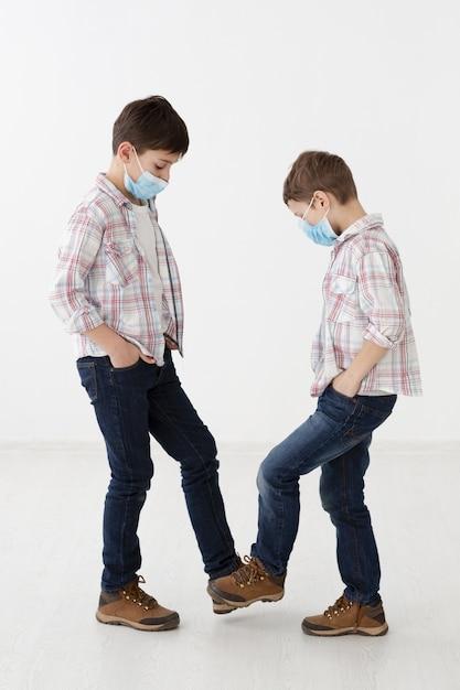 非接触式の挨拶を示す医療用マスクを持つ子供の側面図 無料写真