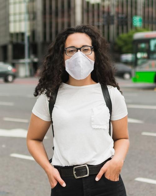 Женщина вид спереди с медицинской маской позирует Бесплатные Фотографии