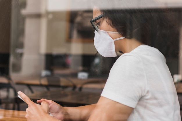 Боком женщина с медицинской маской, проверка ее телефон Бесплатные Фотографии