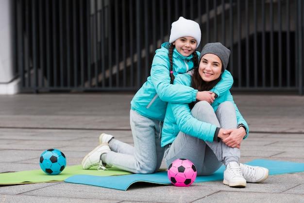 Мать и дочь на коврике обнимаются Бесплатные Фотографии