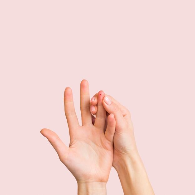 ピンクの背景のクローズアップ手 無料写真
