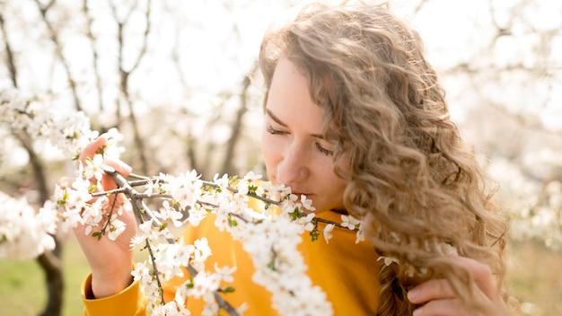 花の臭いがする黄色のシャツを着ている女性 無料写真