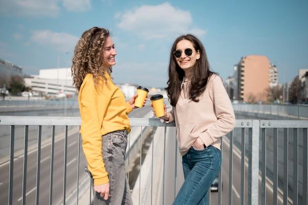 Друзья в темных очках, держа чашку кофе Бесплатные Фотографии
