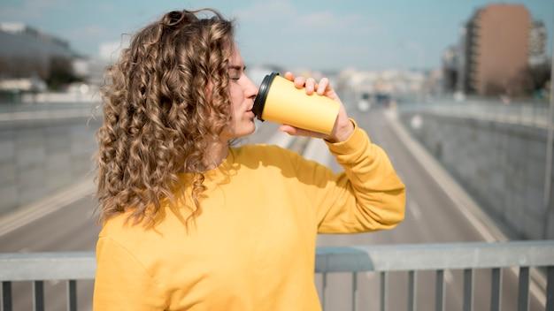 コーヒーからすすりながら黄色のシャツの女性 無料写真