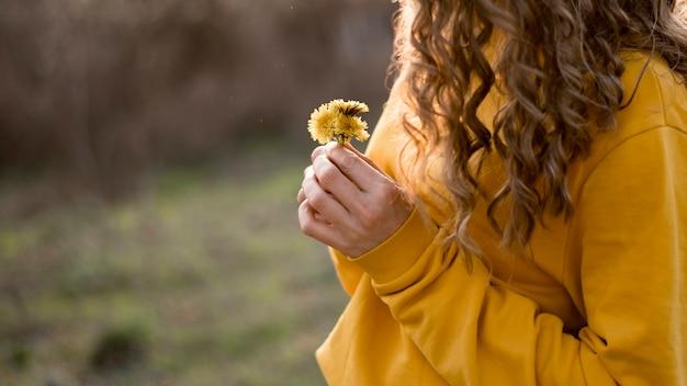 ミディアムビューの花を保持している黄色のシャツの女の子 無料写真
