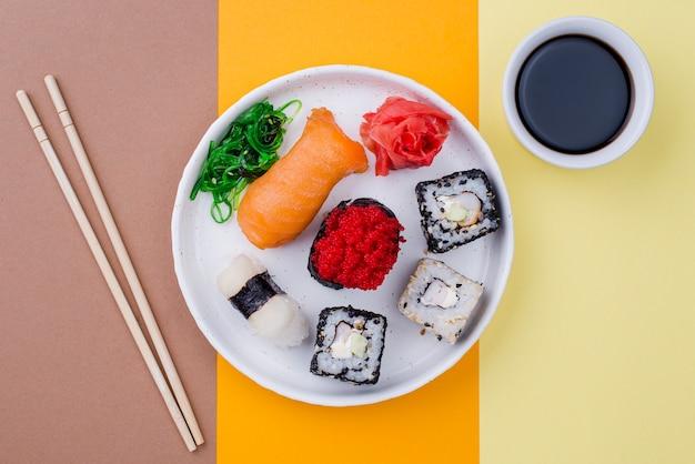 Тарелка с суши и соусом на столе Бесплатные Фотографии