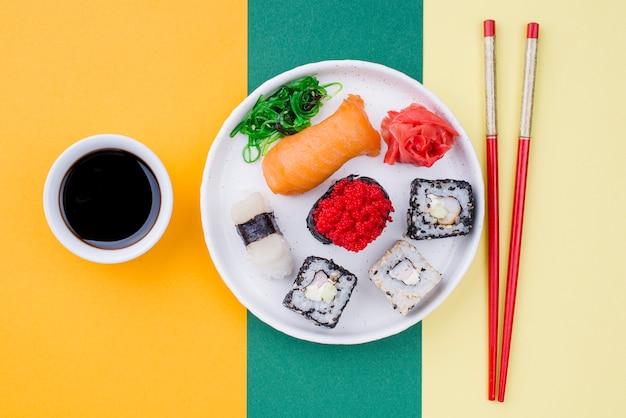 Тарелка с суши и соусом рядом Бесплатные Фотографии