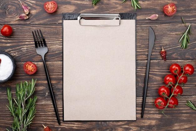 トマトとカトラリーテーブルの上のクリップボード 無料写真