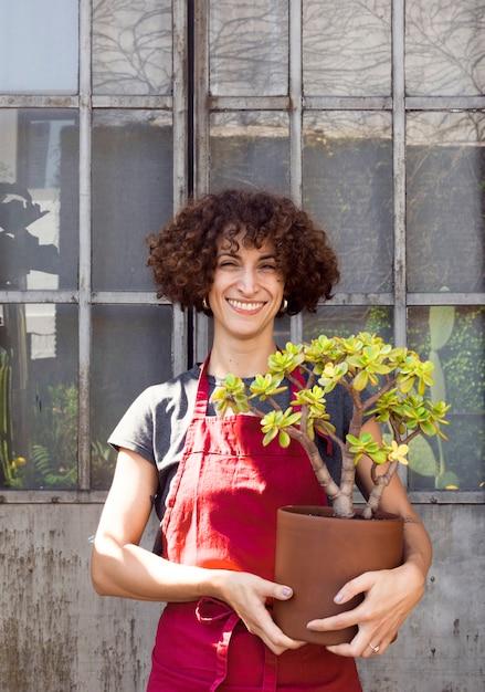 Смайлик женщина, держащая красивое растение Бесплатные Фотографии
