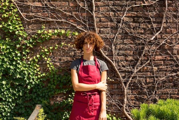 Вид спереди молодая женщина позирует рядом с растениями Бесплатные Фотографии