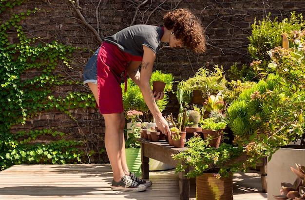 Длинный выстрел женщина заботится о своих растениях Бесплатные Фотографии