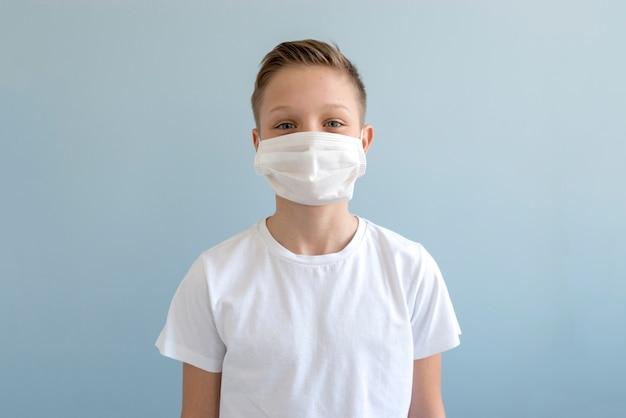 屋内で医療用マスクを着ている少年 無料写真