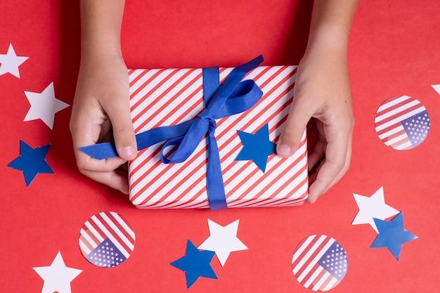 Руки взгляда сверху держа флаг сша обернутый подарок с украшением Бесплатные Фотографии