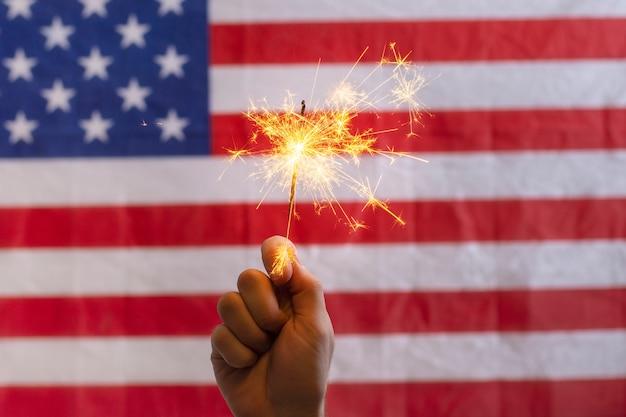 アメリカの国旗の前で線香花火を持っている手 無料写真