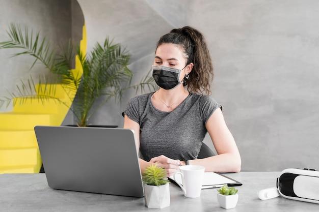 医療マスクを身に着けている営業所の女性 無料写真