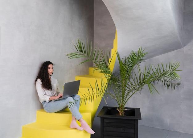 Женщина сидит на лестнице, используя ноутбук Бесплатные Фотографии
