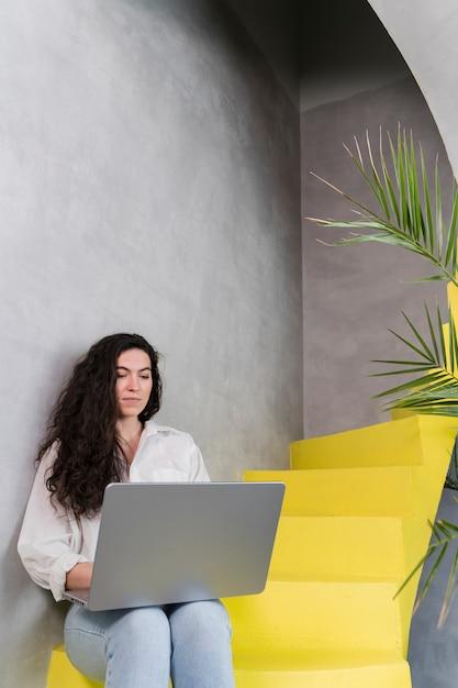 Женщина работает и сидит на лестнице Бесплатные Фотографии