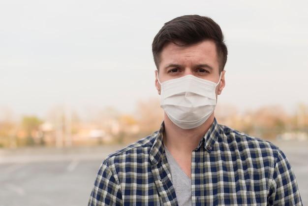 医療マスクを持つ肖像画男 無料写真