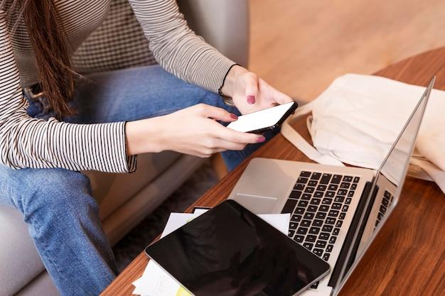 Высокий вид женщины телеработы и с помощью мобильного телефона Бесплатные Фотографии