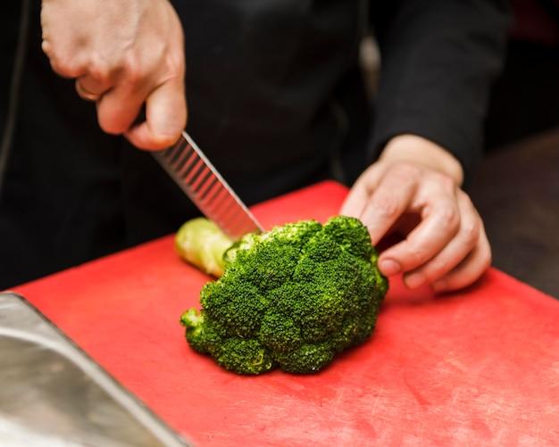 新鮮なブロッコリーを切る人 無料写真