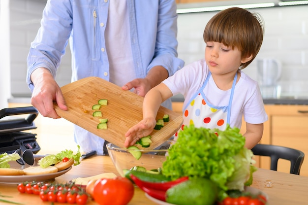 Отец с одним родителем и ребенок кладут овощи в миску Бесплатные Фотографии