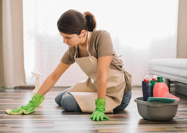 床を掃除して手袋を持つ女性 無料写真