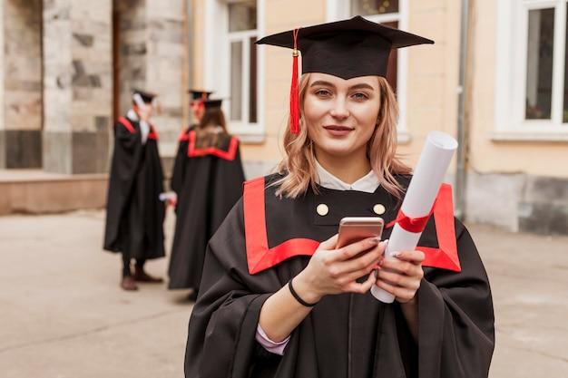 携帯電話をチェックする卒業した女の子 無料写真