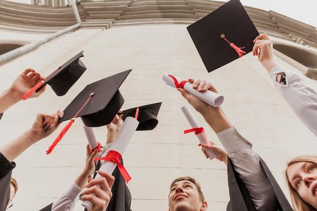 卒業証書を持つ学生のローアングルグループ 無料写真