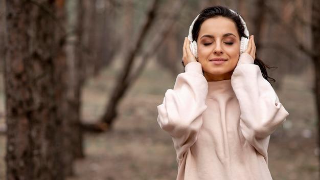 自然の中でヘッドフォンを持つ女性 無料写真